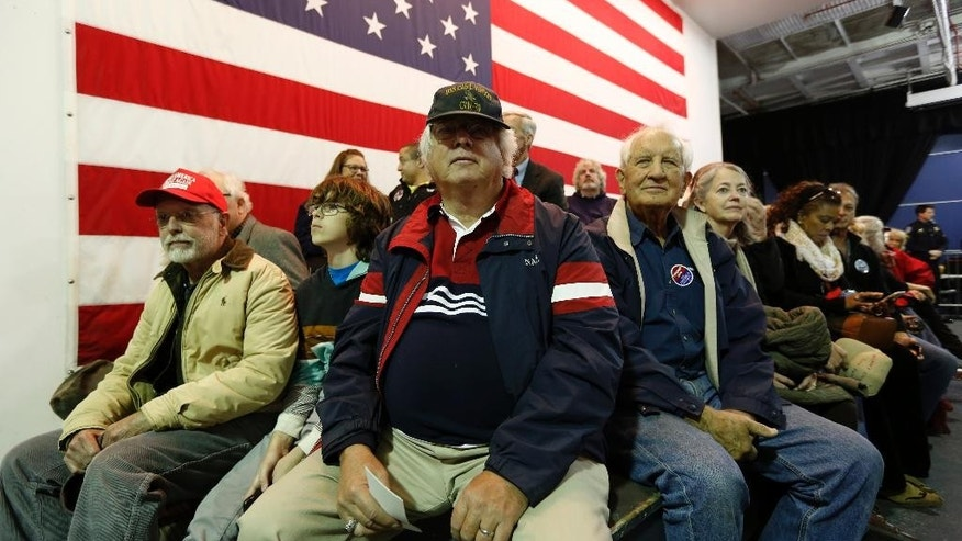 Supporter Erich Schmid, center, from Hilton Head, S.C., waits with other supporters to hear Republican presidential candidate, businessman Donald Trump, speak during a rally coinciding with Pearl Harbor Day at Patriots Point aboard the aircraft carrier USS Yorktown in Mt. Pleasant, S.C., Monday, Dec. 7, 2015. (AP Photo/Mic Smith)