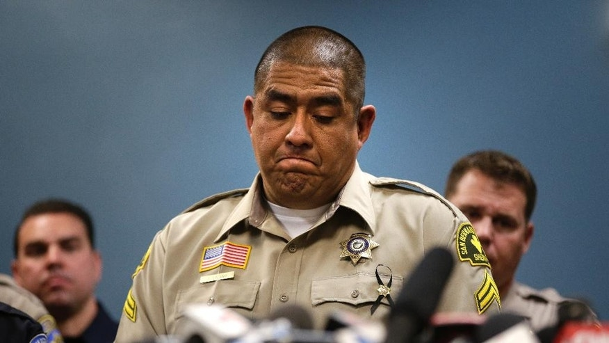 San Bernardino County Sheriff's detective Jorge Lozano, center, pauses while answering questions during a news conference with the first responders on the scene of last week's fatal shooting at a social services center, Tuesday, Dec. 8, 2015, in San Bernardino, Calif. (AP Photo/Jae C. Hong)
