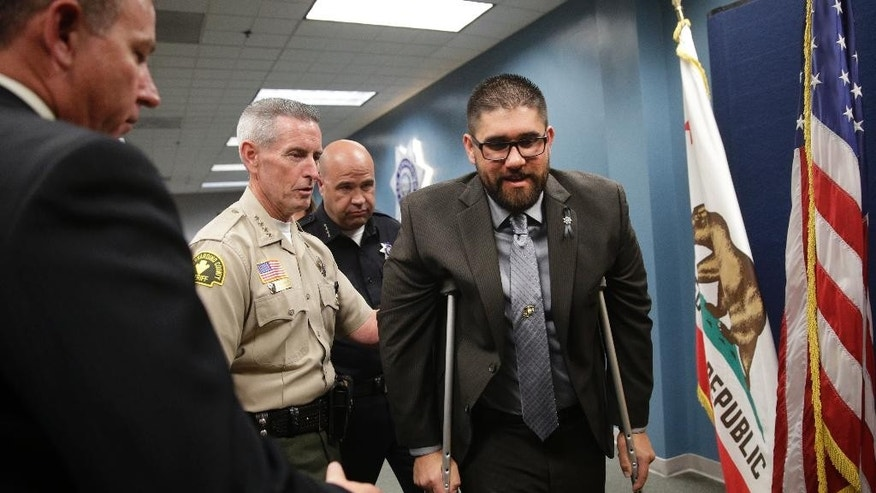 San Bernardino police officer Nicholas Koahou, center, leaves the conference room with San Bernardino County Sheriff John McMahon, second from left, and San Bernardino Police Chief Jarrod Berguan, behind McMahon, after a news conference, Tuesday, Dec. 8, 2015, in San Bernardino, Calif. Koahou was shot in the leg in last week's shootout with the San Bernardino attackers Syed Farook and his wife, Tashfeen Malik. (AP Photo/Jae C. Hong)
