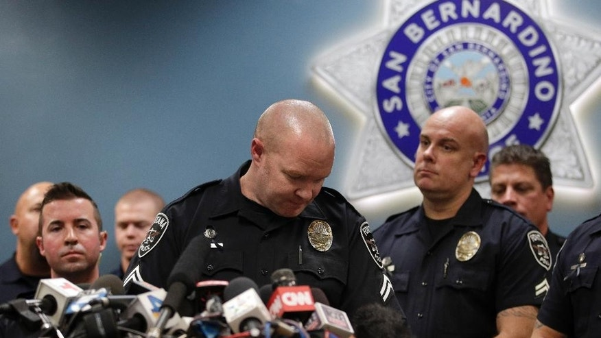 Fontana police corporal Scott Snyder, center, reacts during a news conference with the first responders who were at the scene of last week's fatal shooting at the Inland Regional Center, Tuesday, Dec. 8, 2015, in San Bernardino, Calif. (AP Photo/Jae C. Hong)