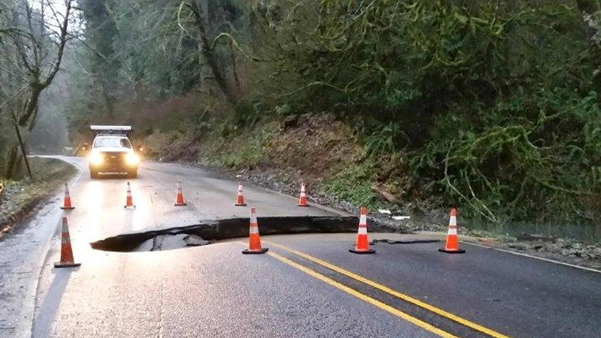 This photo released by the Oregon Department of Transportation shows a sinkhole on Highway 22 in Yamhill County, Ore., Tuesday, Dec. 8, 2015. The National Weather Service on Monday issued a flood watch for much of northwest Oregon and southwest Washington. (Oregon Department of Transportation via AP)