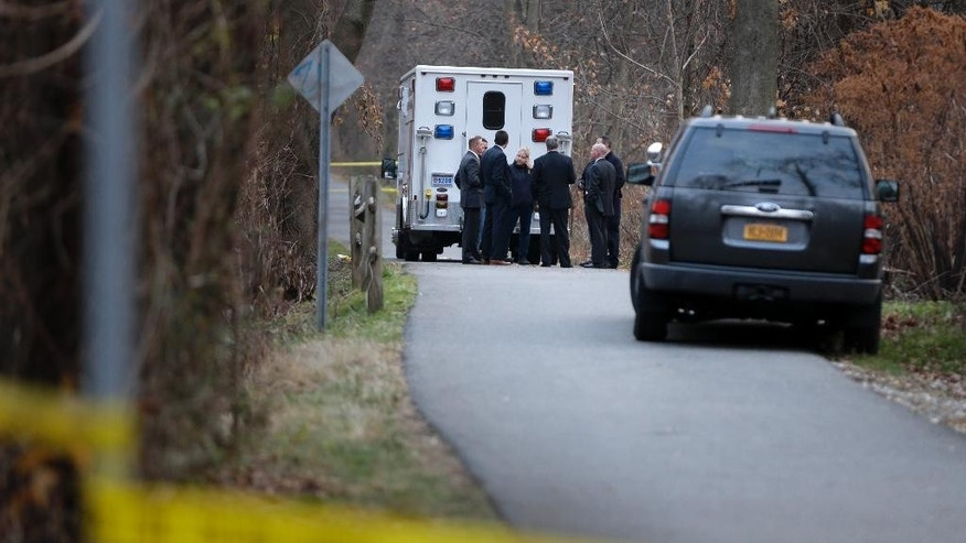 Police officers and investigators stand near the scene of a fatal shooting in Yonkers, N.Y., Wednesday, Dec. 9, 2015.  State special prosecutors are overseeing the investigation into the fatal shooting of a man in a confrontation with New York City police in Westchester County. The encounter happened after a police chase that ended in a crash on a busy suburban parkway. (AP Photo/Seth Wenig)