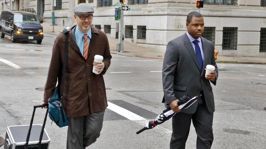 FILE - In this Dec. 2, 2015, file photo, Baltimore City police officer William Porter, right, one of six Baltimore police officers charged with the death of Freddie Gray, walks to the courthouse with one of his attorneys in Baltimore. Porter faces manslaughter, assault, misconduct in office and reckless endangerment charges. (Kevin Richardson/The Baltimore Sun via AP, File) WASHINGTON EXAMINER OUT; MANDATORY CREDIT