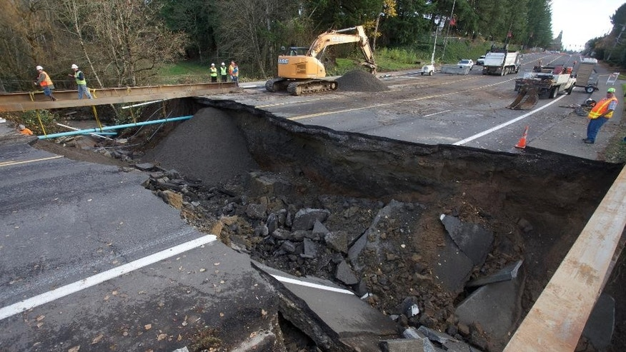 Maintenance personnel look at a large sinkhole on Kane Drive in Gresham, Ore., Wednesday, Dec. 9, 2015.Torrential rains pummeled parts of the Pacific Northwest early Wednesday, causing mudslides and flooding roads. (AP Photo/Steve Dipaola)