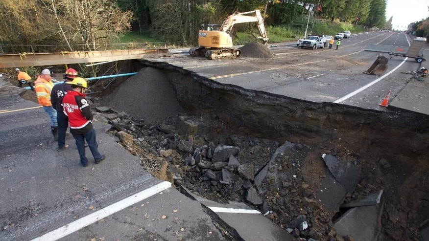 Fire and maintenance personnel look at a large sinkhole on Kane Drive in Gresham, Ore., Wednesday, Dec. 9, 2015. Torrential rains pummeled parts of the Pacific Northwest early Wednesday, causing mudslides and flooding roads.(AP Photo/Steve Dipaola)