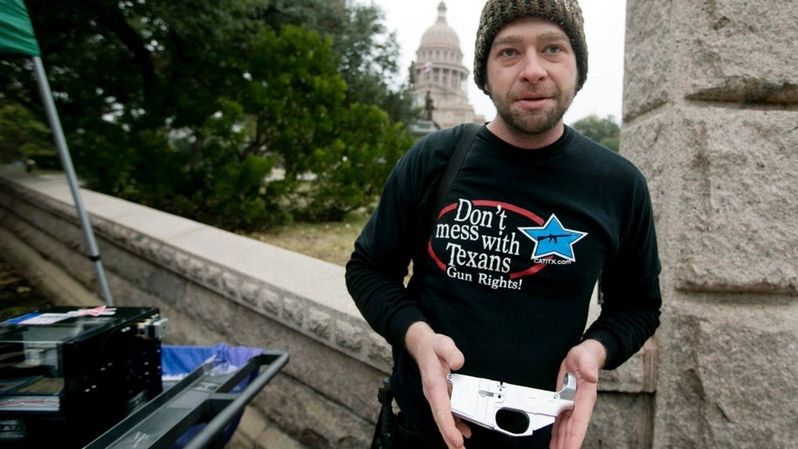 In this photo taken on Jan. 13, 2015, Matthew Short , public relations director with Come and Take It Texas and DontComply.com, shows the incomplete AR-15 lower receiver which was to be completed by the Ghost Cutter CNC machine, at left, by Defense Distributed at a rally to support HB195, the open carry bill, at the Capitol in Austin.