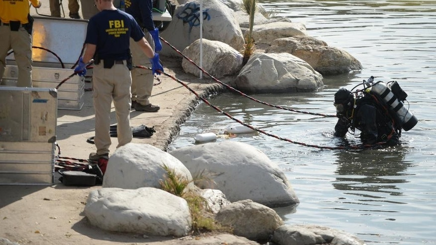 Members of the FBI Underwater Search and Evidence Response Team work in Seccombe Lake on Thursday, Dec. 10, 2015 in San Bernardino, Calif. (Micah Escamilla/The Sun via AP) MANDATORY CREDIT