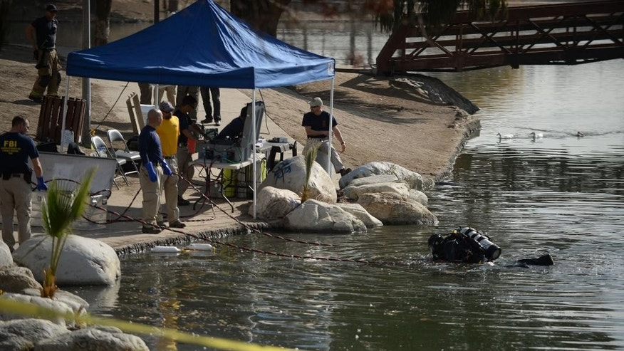 Members of the FBI Underwater Search and Evidence Response Team and bomb specialists work at Seccombe Lake on Thursday, Dec. 10, 2015 in San Bernardino, Calif. (Micah Escamilla/The Sun via AP) MANDATORY CREDIT