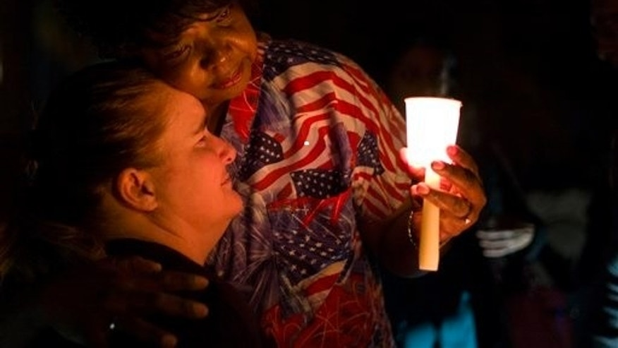"Lisa Hamons, front, a social worker for San Bernardino County, is hugged by Yolanda Richardson during a candlelight vigil for shooting victims on Monday, Dec. 7, 2015, in San Bernardino, Calif. The husband and wife who opened fire on a social services center last week had been radicalized ""for quite some time"" and had taken target practice at area gun ranges, in one instance just days before the attack that left 14 people dead, the FBI said Monday. (AP Photo/Jae C. Hong)"