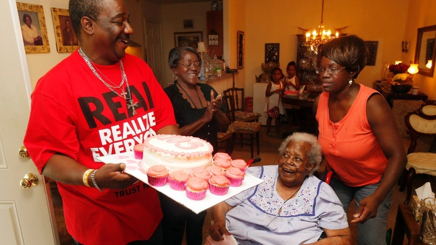 "FILE- In this July 25, 2015, file photo, Terrance Jackson, left, Doris Ware, second from left, and Beverly Booker, right, sing ""Happy Birthday To You"" to Bernice Williams, seated, as she celebrates her 103rd birthday in the Mill City neighborhood of Dallas."