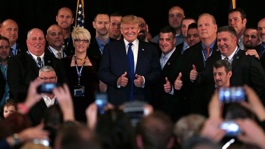 Republican presidential candidate Donald Trump flashes thumbs up after being endorsed at a regional police union meeting in Portsmouth, N.H., Thursday, Dec. 10, 2015. (AP Photo/Charles Krupa)