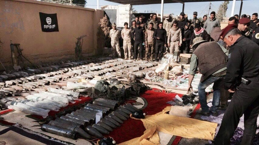 Iraqi security forces look at confiscated Islamic State group weapons and ammunition after regaining control over the last week, in Ramadi, Iraq's Anbar province, 70 miles (115 kilometers) west of Baghdad, Thursday, Dec. 10, 2015. Following significant advances on Ramadi Tuesday, Iraqi forces are now preparing to push into the city center from the southwest and the north. Tuesday's advances, the most significant incursion into Ramadi since the city fell to the Islamic State group in May, have placed Iraqi forces along the southwest edge of Ramadi in the Tamim neighborhood and just north of the city at the former Anbar operations command. An Islamic State flag is seen hung upside down. (AP Photo/Osama Sami)
