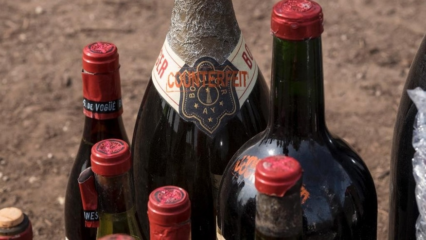 "The word ""counterfeit"" is stamped on a few of the 500 plus bottles of wine destroyed by the U.S. Marshals Asset Forfeiture Division at the Texas Disposal Systems recycling and compost facility in Austin, Texas, Thursday, Dec. 10, 2015. The wine is from the Rudy Kurniawan case, the man convicted of fraud in federal court in 2013 for producing and selling millions of dollars of counterfeit wine. (Rodolfo Gonzalez/Austin American-Statesman via AP)  AUSTIN CHRONICLE OUT, COMMUNITY IMPACT OUT, INTERNET AND TV MUST CREDIT PHOTOGRAPHER AND STATESMAN.COM, MAGS OUT; MANDATORY CREDIT"