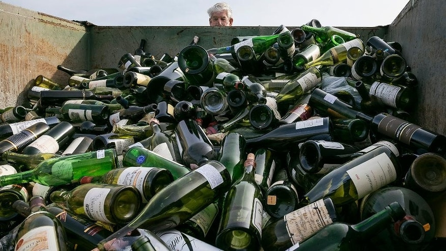 More than 500 bottles of counterfeit and unsellable wine are destroyed at the Texas Disposal Systems recycling and compost facility in Austin, Texas, on Thursday, Dec. 10, 2015. The wine is from the Rudy Kurniawan case, the man convicted of fraud in federal court in 2013 for producing and selling millions of dollars of counterfeit wine. (Rodolfo Gonzalez/Austin American-Statesman via AP)  AUSTIN CHRONICLE OUT, COMMUNITY IMPACT OUT, INTERNET AND TV MUST CREDIT PHOTOGRAPHER AND STATESMAN.COM, MAGS OUT; MANDATORY CREDIT