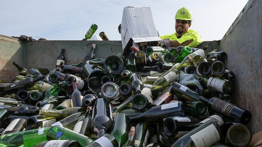 Kevin Benavides, left, and Isidoro Guerra, right, and with Texas Disposal Systems dump more than 500 counterfeit or unsellable wine bottles into a dumpster to be destroyed by the US Marshals Asset Forfeiture Division at the Texas Disposal Systems recycling and compost facility in Austin, Texas, Thursday, Dec. 10, 2015. The wine is from the Rudy Kurniawan case, the man convicted of fraud in federal court in 2013 for producing and selling millions of dollars of counterfeit wine.  (Rodolfo Gonzalez/Austin American-Statesman via AP)  AUSTIN CHRONICLE OUT, COMMUNITY IMPACT OUT, INTERNET AND TV MUST CREDIT PHOTOGRAPHER AND STATESMAN.COM, MAGS OUT; MANDATORY CREDIT