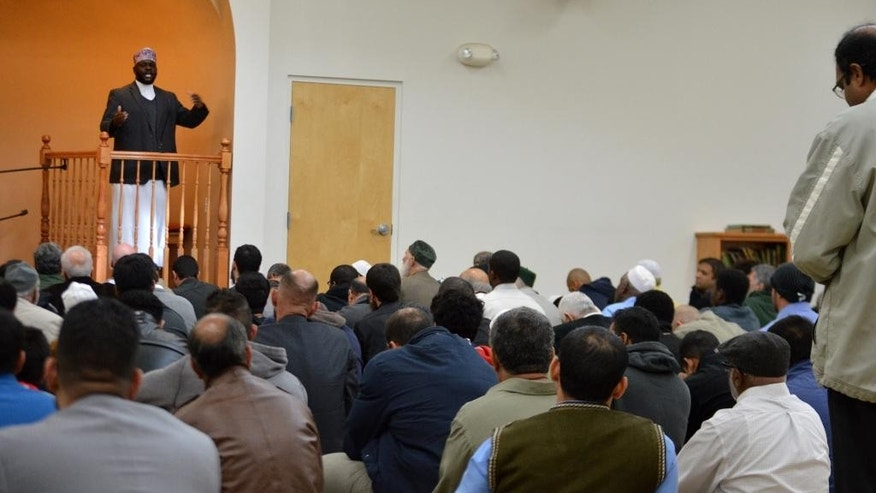 "Imam Shafi Abdul Aziz, left, of the the Islamic Center of New Mexico in Albuquerque, speaks on the importance of tolerance during afternoon prayer Friday, Dec. 11, 2015. A coalition of Christian and Jewish leaders presented the Albuquerque mosque dozens of ""letters of support"" after GOP presidential hopeful Donald Trump suggested the U.S. place a moratorium on Muslim immigration. (AP Photo/Russell Contreras)"