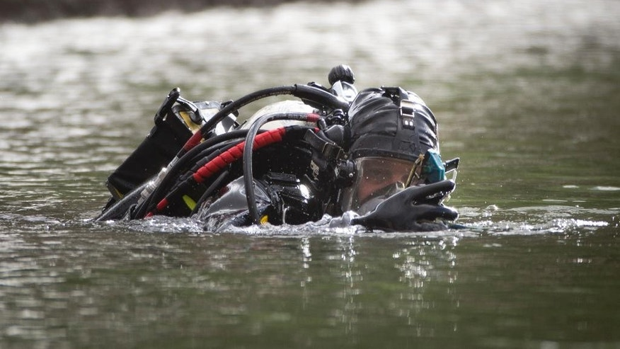 A member of the FBI dive team searches Seccombe Lake for evidence in connection with last week's fatal shooting at Inland Regional Center, Friday, Dec. 11, 2015, in San Bernardino, Calif. The FBI says divers are searching the lake in a San Bernardino park because leads indicate the shooters who killed several people at a holiday party had been in the area. (AP Photo/Jae C. Hong)