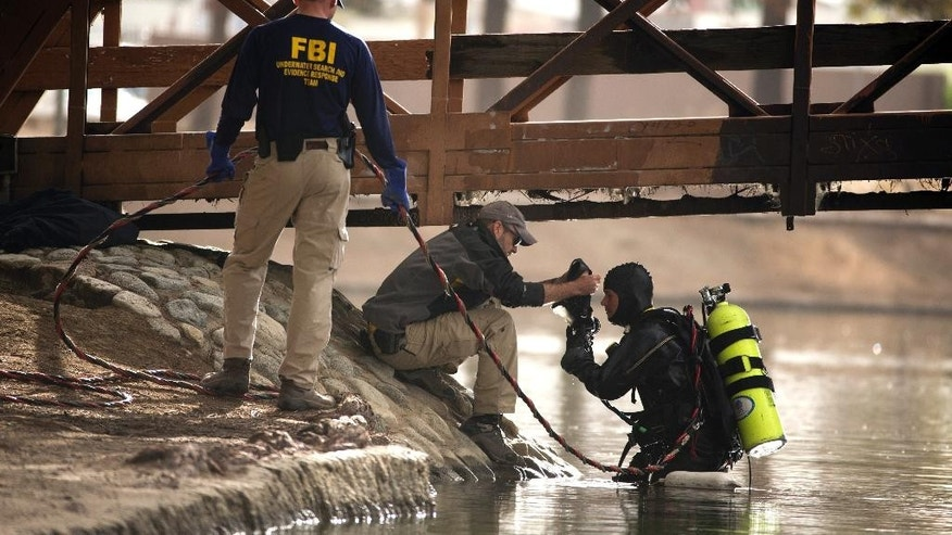 An FBI dive team prepares to search Seccombe Lake for evidence in connection with last week's fatal shooting at Inland Regional Center , Friday, Dec. 11, 2015, in San Bernardino, Calif. The FBI says divers are searching the lake in a San Bernardino park because leads indicate the shooters who killed 14 people at a holiday party had been in the area. (AP Photo/Jae C. Hong)