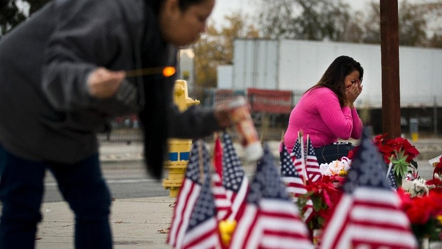 Ginger Sizemore, right, breaks down while paying her respects at a makeshift memorial near the Inland Regional Center, Friday, Dec. 11, 2015, in San Bernardino, Calif. Authorities said Syed Rizwan Farook and his wife Tashfeen Malikkilled shot and killed several people at a holiday gathering at the center on Dec. 2.  (AP Photo/Jae C. Hong)