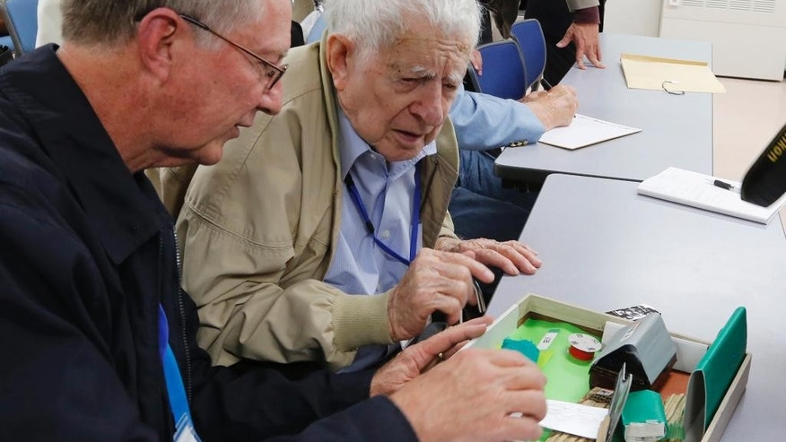 Scott Downing, 96, of Amarillo, TX, center, accompanied by his son, Stuart, looks at a model of the area where his plane crashed at a community hall during his retrospective visit to Inzai, a town 40 kilometers (25 miles) northeast of Tokyo, where he was taken prisoner of war 70 years ago, Friday, Dec. 11, 2015. Three of the 11-member crew were killed that night of May 25, 1945, when their B-29 was shot down, crashing into bamboo groves as they were flying back from a bombing raid on Tokyo. In an emotional moment, Downing was given a hero's welcome by Inzai, which had given the U.S. airmen proper burials at a temple and mourned their deaths, defying the stereotypes about wartime animosity. (AP Photo/Yuri Kageyama)