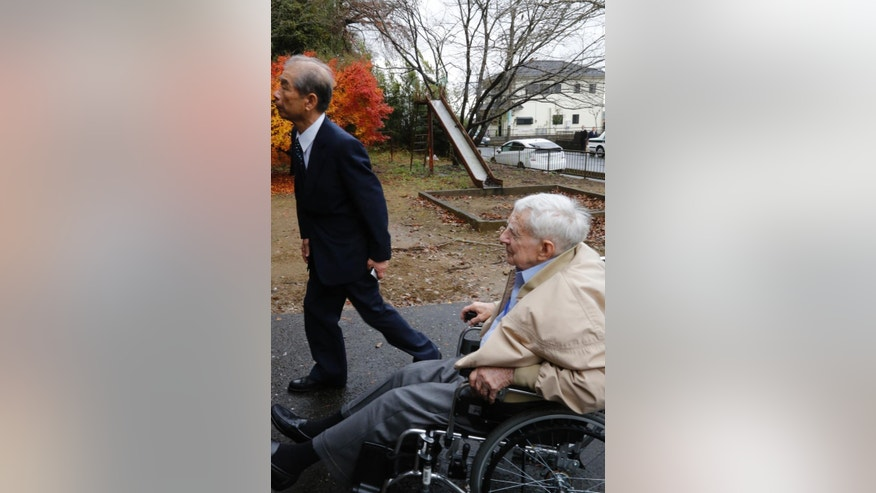 Scott Downing, 96, of Amarillo, TX, seated in a wheelchair, arrives at a temple with Japanese researcher Isao Arai during his retrospective visit to Inzai, a town 40 kilometers (25 miles) northeast of Tokyo, where he was taken prisoner of war 70 years ago, Friday, Dec. 11, 2015. Three of the 11-member crew were killed that night of May 25, 1945, when their B-29 was shot down, crashing into bamboo groves as they were flying back from a bombing raid on Tokyo. Downing was among eight who parachuted to safety, only to be taken prisoner, beaten, half-starved and interrogated by Japan's Imperialist military during the closing months of the war. In an emotional moment, Downing was given a hero's welcome by Inzai, which had given the U.S. airmen proper burials at a temple and mourned their deaths, defying the stereotypes about wartime animosity. (AP Photo/Yuri Kageyama)
