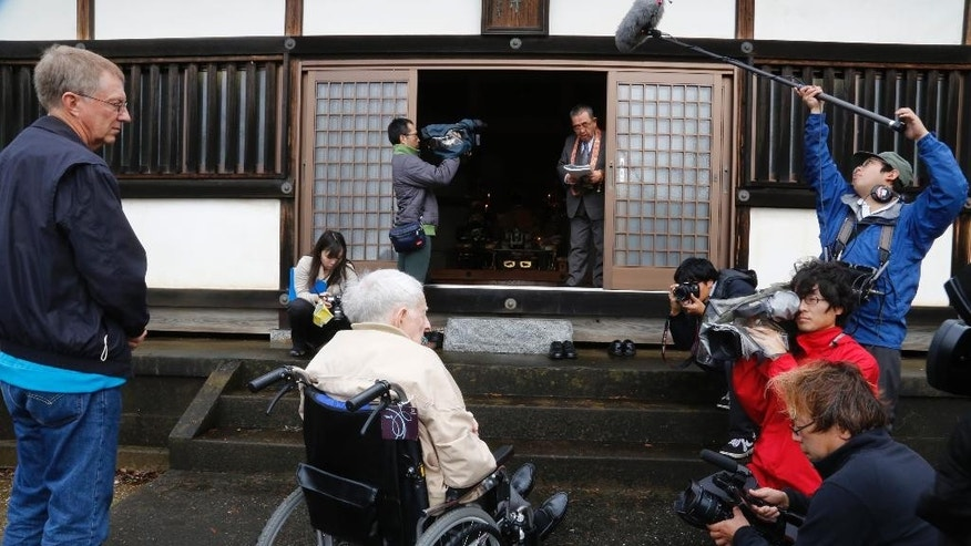 Scott Downing, 96, of Amarillo, TX, seated in a wheelchair, accompanied by his son, Stuart, left, is filmed by the media while listening to a monk at a temple during his retrospective visit to Inzai, a town 40 kilometers (25 miles) northeast of Tokyo, where he was taken prisoner of war 70 years ago, Friday, Dec. 11, 2015. Three of the 11-member crew were killed that night of May 25, 1945, when their B-29 was shot down, crashing into bamboo groves as they were flying back from a bombing raid on Tokyo. Downing was among eight who parachuted to safety, only to be taken prisoner, beaten, half-starved and interrogated by Japan's Imperialist military during the closing months of the war. In an emotional moment, Downing was given a hero's welcome by Inzai, which had given the U.S. airmen proper burials at a temple and mourned their deaths, defying the stereotypes about wartime animosity. (AP Photo/Yuri Kageyama)
