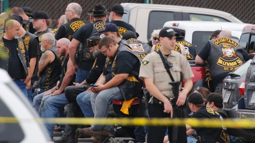 May 17, 2015: A McLennan County deputy stands guard near a group of bikers in the parking lot of a Twin Peaks restaurant, in Waco, Texas.