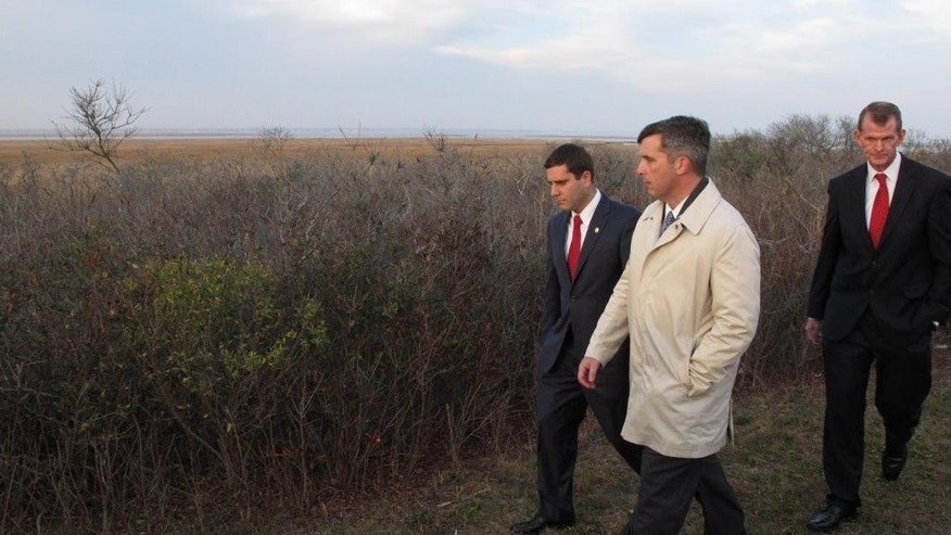 "Deputy Suffolk County Police Commissioner Tim Sini, left, homicide Detective Lt. Kevin Beyrer, center, and Chief of Department Stuart Cameron tour a remote area off a Long Island parkway Friday, Dec. 11, 2015, where the bodies of 10 people were discovered in 2010 and 2011, in Babylon, N.Y. Sini, who has been nominated to be the new police commissioner, has announced a renewed effort at finding those responsible for the killings in what has become known as the ""Long Island serial killer"" case. Friday marked the fifth anniversary of when the first of the victims were found. The body of an 11th woman also was found several miles away, but detectives do not believe her death is linked to the other 10. (AP Photo/Frank Eltman)"
