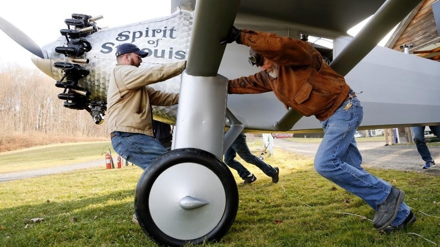 In this Sunday, Dec. 6, 2015 photo, Clay Hammond, left, and Ken Cassens help move a Spirit of St. Louis replica to a runway at Old Rhinebeck Aerodrome in Rhinebeck, N.Y. Cassens has spent years creating a doppelganger of the plane Charles Lindbergh flew across the Atlantic in 1927 down to every flap and fuel gauge. (AP Photo/Mike Groll)
