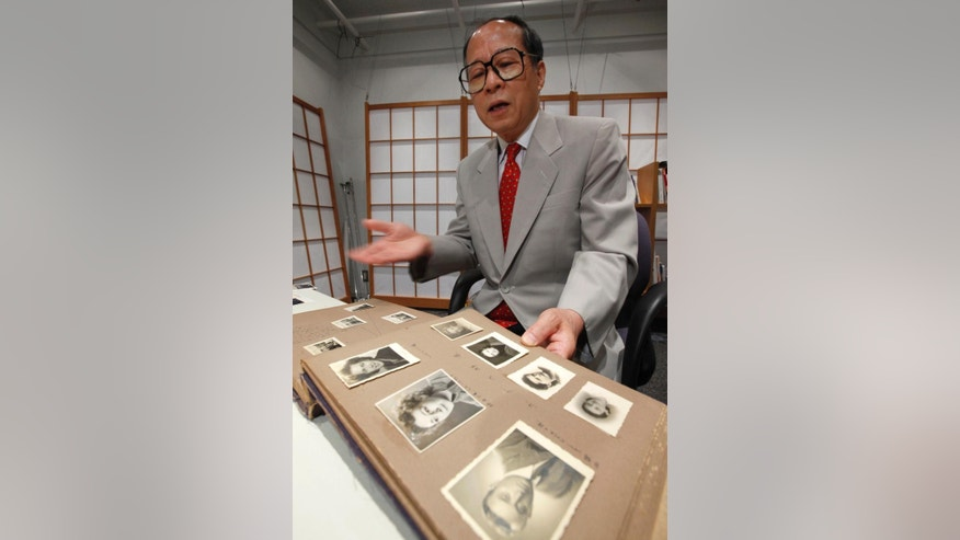 FILE - In this July 26, 2010 file photo, Akira Kitade displays a photo album that belonged to a former colleague of his at the  Japan Tourist Bureau, Tatsuo Osako, during an interview in Tokyo. The page in the foreground holds seven photos given to Osako by people whom Osako helped escape from Europe in the early days of World War II. Kitade, with the help of researchers in Japan and the U.S., has identified four of the seven people this year. A fifth was identified independently in 2014. Kitade met recently in the New York City area with descendants of three of the refugees who have been identified. (AP Photo/Shizuo Kambayashi, File)