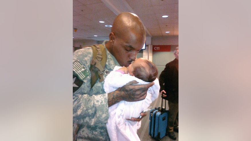 In this photo provided by Dinetta Scott, James Brown holds his month-old daughter Jayliah right before Brown was returning to Iraq in 2010 for deployment. The daughter is a month old at the time. Army Sgt. James Brown survived two tours of combat duty in Iraq. He died in a West Texas jail in 2012 while serving a weekend sentence for a DWI conviction. (Courtesy Dinetta Scott via AP)