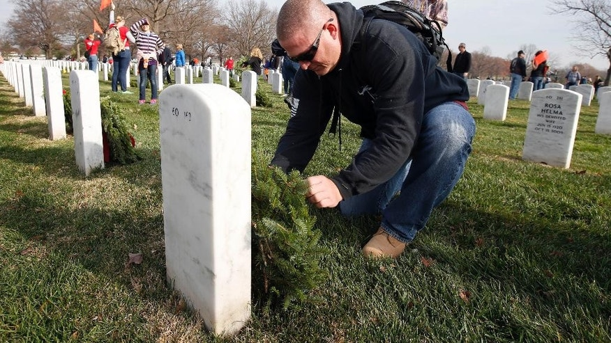 A crowd of volunteers gathers around a truck to get wreaths to place at graves as part of Wreaths Across America at Arlington National Cemetery, Saturday, Dec. 12, 2015 in Arlington, Va. Organizers estimated that volunteers placed 240,815 wreaths at Arlington. (AP Photo/Alex Brandon)