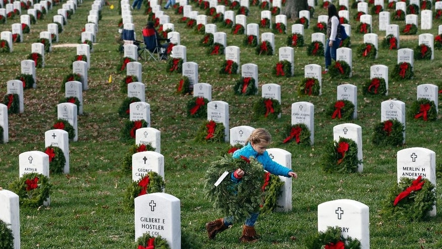 Lane Austin, 6, of Virginia Beach, Va., carries a wreath to grave during Wreaths Across America at Arlington National Cemetery, Saturday, Dec. 12, 2015 in Arlington, Va. Organizers estimated that volunteers placed 240,815 wreaths at Arlington.(AP Photo/Alex Brandon)