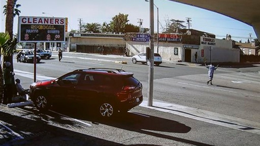 Dec. 12, 2015: In this image made from security video footage provided by the Los Angeles County Sheriff, a man, right, walks with a gun in his hand in Lynwood, Calif.