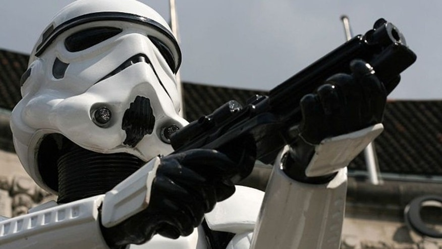 "A Stormtrooper of the ""Star Wars"" franchise  holds a rebel blaster."