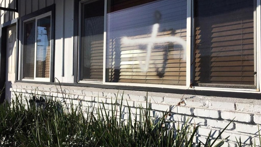 This photo provided by the Ahmadiyya Muslim Community muslimsforpeace.org shows crosses in spray paint vandalizing windows at the Ahmadiyya Muslim Community Baitus-Salaam Mosque in Hawthorne, Calif., Sunday, Dec. 13, 2015. The FBI is investigating after police in Hawthorne say two mosques in that city were vandalized with paint, and a fake grenade was left in the driveway of one of the properties.(Ahmadiyya Muslim Community muslimsforpeace.org via AP)