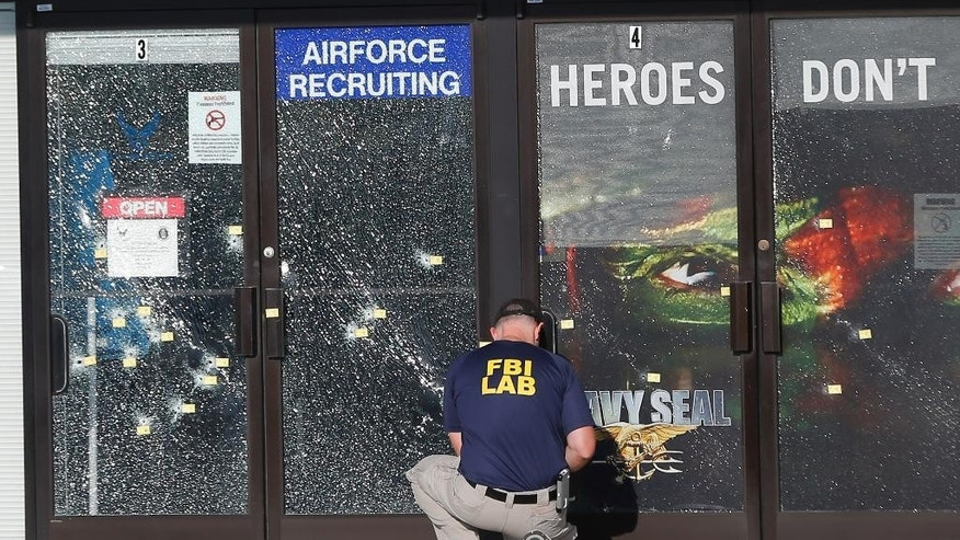 In this July 17 photo, an FBI investigator investigates the scene of a shooting outside a military recruiting center in Chattanooga.