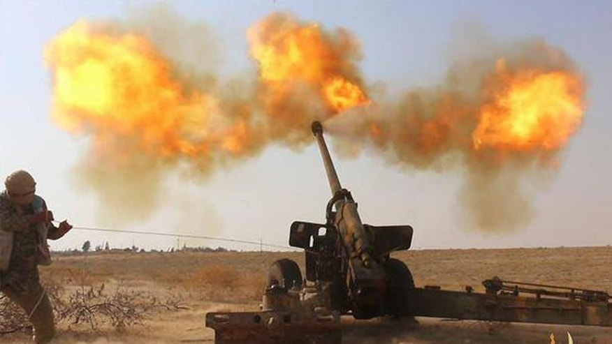 In this image posted online June 23, 2015 by supporters of the Islamic State militant group on an anonymous photo sharing website, an Islamic State militant fires artillery against Syrian government forces in Hama city, Syria. (Militant website via AP)