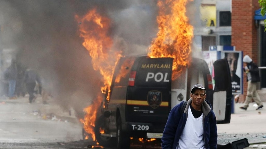 FILE - In this Monday, April 27, 2015 file photo, a man walks past a burning police vehicle amid unrest following the funeral of Freddie Gray in Baltimore. Gray died from spinal injuries about a week after he was arrested and transported in a Baltimore Police Department van. (AP Photo/Patrick Semansky)