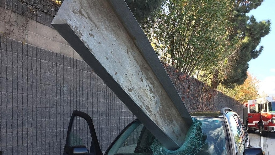 This Friday, Dec. 11, 2015 photo provided by the San Jose Fire Department shows a beam that fell off of a flatbed truck that impaled the window of a BMW car on I-280 in San Jose, Calif. The driver of the BMW, Don Lee, suffered only a small scratch to his right arm. (Courtesy San Jose Fire Department via AP) MANDATORY CREDIT