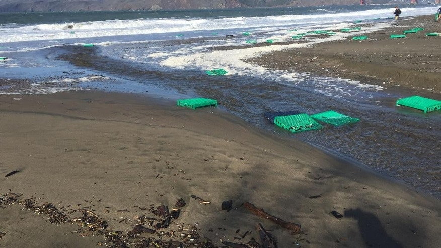 This photo provided by Drew Laughlin shows debris from a shipping container after being washed ashore in San Francisco's Baker beach on Sunday, Dec. 13, 2015. The U.S. Coast Guards says 12 containers, most of them empty, were washed overboard of a cargo ship just outside the Golden Gate Bridge Friday because of stormy seas. (AP Photo/Drew Laughlin)