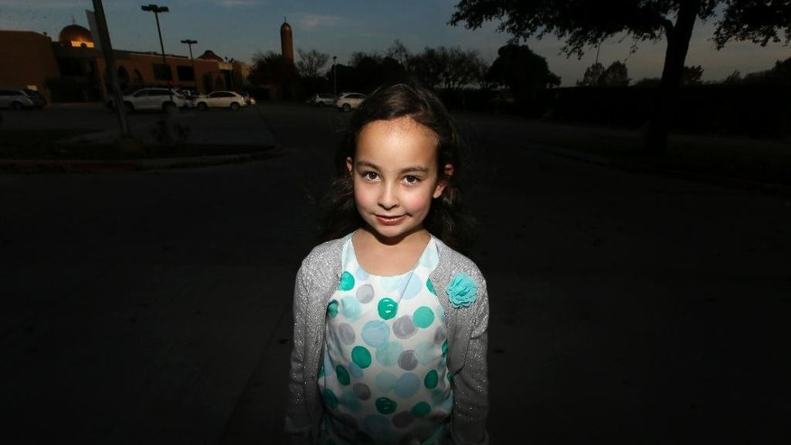Sofia Yassini, 8, poses for a photo outsider a mosque in Richardson, Texas, Friday, Dec. 11, 2015. After seeing presidential candidate Donald Trump call on television for barring Muslims from entering the country, the 8-year-old started packing her favorite things and checking the locks on the doors because, in her mind, Donald Trump's push to ban Muslims entering the country meant the Army would come and rip her family from their home. Trumps remarks in the wake of the Dec. 2  shooting attack in San Bernardino, Calif., have stoked similar fears in Muslim children across the U.S. Their young minds, parents say, are confused about who the screaming man on TV is, what he's saying about their faith and why thousands of their fellow Americans are cheering him on. (AP Photo/LM Otero)