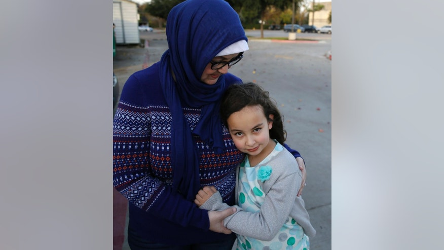 Sofia Yassini, 8, right, gets a hug from her mother Melissa Yassini after posing for a photo outsider a mosque in Richardson, Texas, Friday, Dec. 11, 2015. After seeing presidential candidate Donald Trump call on television for barring Muslims from entering the country, the 8-year-old started packing her favorite things and checking the locks on the doors because, in her mind, Donald Trump's push to ban Muslims meant the Army would come and rip her family from their home. Trumps' remarks in the wake of the Dec. 2  shooting attack in San Bernardino, Calif., have stoked similar fears in Muslim children across the U.S. Their young minds, parents say, are confused about who the screaming man on TV is, what he's saying about their faith and why thousands of their fellow Americans are cheering him on. (AP Photo/LM Otero)