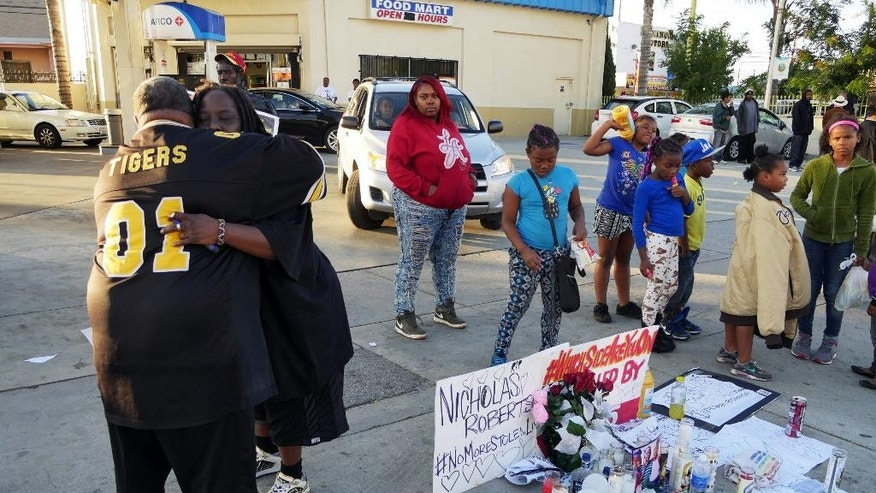 Latrice Barkus, Nicholas Robertson's aunt, facing camera, is embraced in front of the sidewalk memorial set up to honor her nephew on Sunday, Dec. 13, 2015, in Lynwood, Calif. Robertson was fatally shot Saturday by Los Angeles County Sheriff's deputies in Lynwood, south of Los Angeles. Authorities said Robertson was shot after he refused to drop a gun he was carrying. (AP Photo/David Martin)