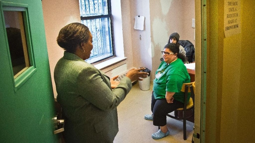 "Cynthia Isaac-Gueye, left, director of Mental Health and Health Home Services at Haven apartments, drops in on a meeting on-site between a resident and social worker, Tuesday, Dec. 8, 2015, Bronx, N.Y.  Facing a swell in homelessness, the city is embarking on investing in ""supportive housing"" like Haven, where homeless and mentally ill residents have their own apartments with on-site service. (AP Photo/Bebeto Matthews)"