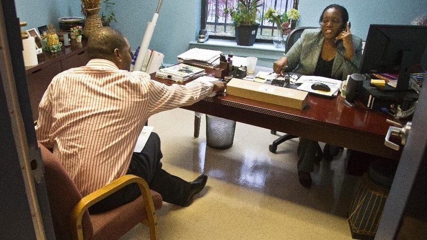 "Cynthia Isaac-Gueye, right, director of Mental Health and Health Home Services, meets with Daniel Stone, left, clinical supervisor at Haven apartments, Tuesday, Dec. 8, 2015, Bronx, N.Y.  Facing a swell in homelessness, the city is embarking on investing in ""supportive housing"" like Haven, where homeless and mentally ill residents have their own apartments with on-site service. (AP Photo/Bebeto Matthews)"