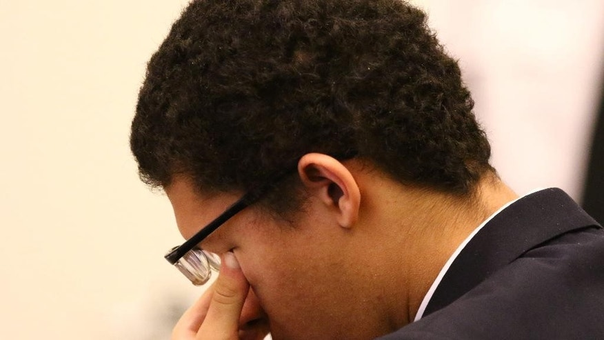 """Philip Chism rubs his eyes during closing arguments of his murder trial in Salem Superior Court, Monday, Dec. 14,2015, during closing arguments. The Massachusetts teenager who raped and killed his high school math teacher """"knew right from wrong and could choose right from wrong,"""" a prosecutor said Monday during closing arguments in the teen's murder trial. (Mark Lorenz/The Boston Herald via AP, Pool)"""