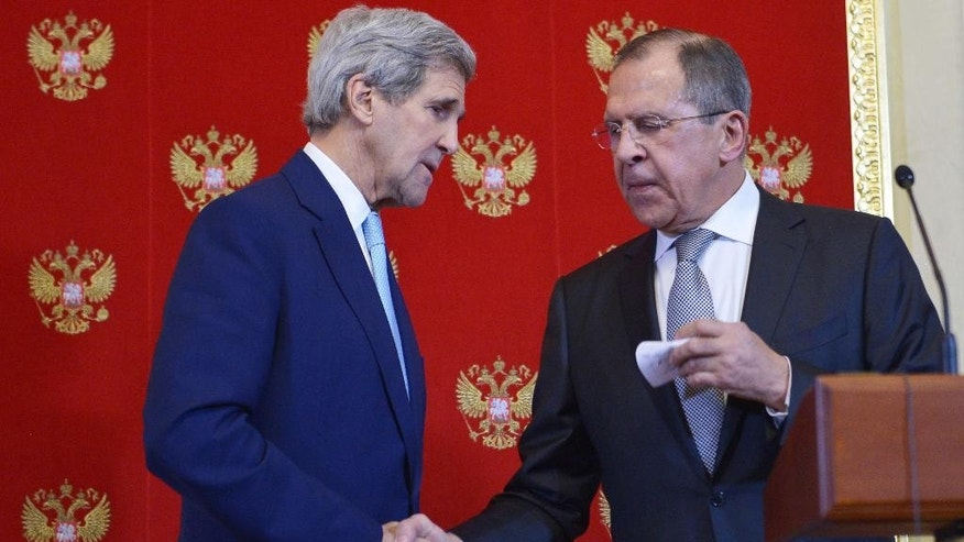 US Secretary of State, John Kerry, left, and Russia's Foreign Minister, Sergey Lavrov, shake hands during a joint press conference at the Kremlin, Tuesday, Dec. 15, 2015 in Moscow. Earlier, in talks with Russian Foreign Minister Sergey Lavrov, Kerry said the world benefits when great powers agree in their approaches to major crises. (Mandel Ngan/Pool Photo via AP)