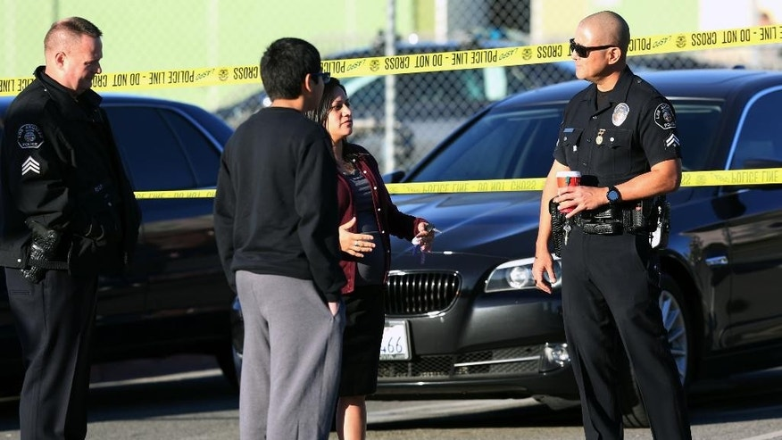 Police officers explain to a parent and her son that his school was closed for the day at Edward Roybal High School in Los Angeles, on Tuesday morning, Dec. 15, 2015. All schools in the vast Los Angeles Unified School District, the nation's second largest, have been ordered closed due to an electronic threat Tuesday. (AP Photo/Richard Vogel)