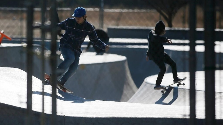 Skateboarders perform tricks at Pedlow Field Skate Park before the park opens as LAUSD schools remain closed, Tuesday, Dec. 15, 2015, in Encino, Calif. All schools in the vast Los Angeles Unified School District, the nation's second largest, have been ordered closed due to an electronic threat Tuesday. (AP Photo/Danny Moloshok)